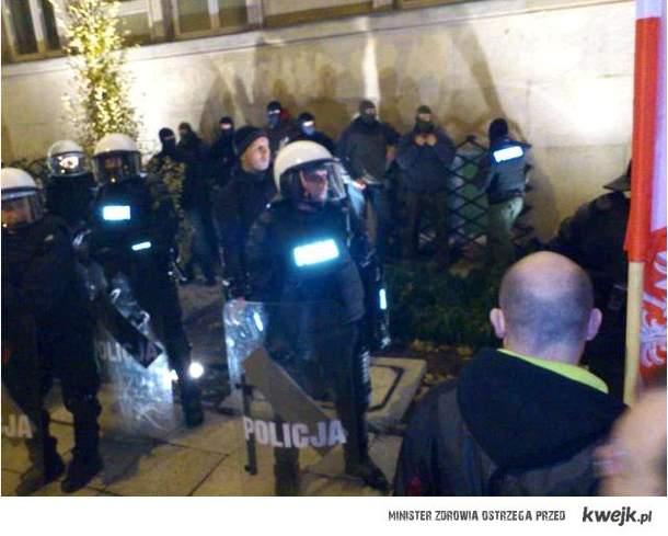 Prowokatorzy w kominiarkach stojący za osłoną policji